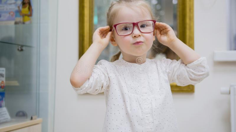 Little girl tries fashion medical glasses near mirror - shopping in ophthalmology clinic. Close up royalty free stock photos