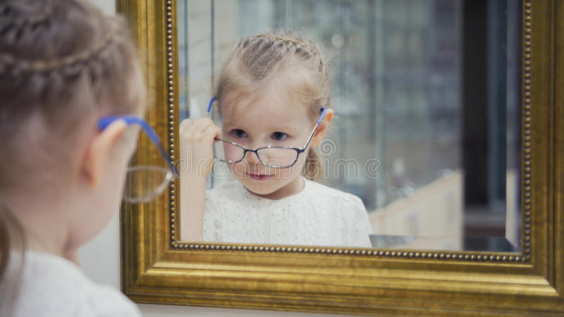 Little girl tries new glasses near mirror - shopping in ophthalmology clinic. Close up royalty free stock photography