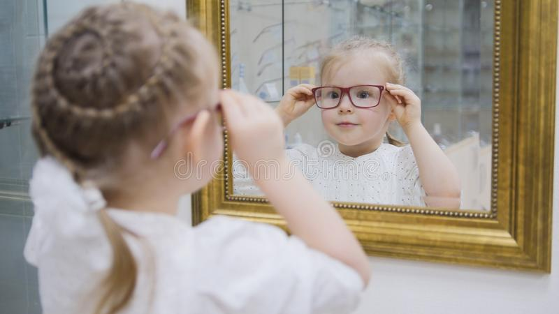 Little girl tries new glasses near mirror - shopping in ophthalmology clinic. Close up stock images