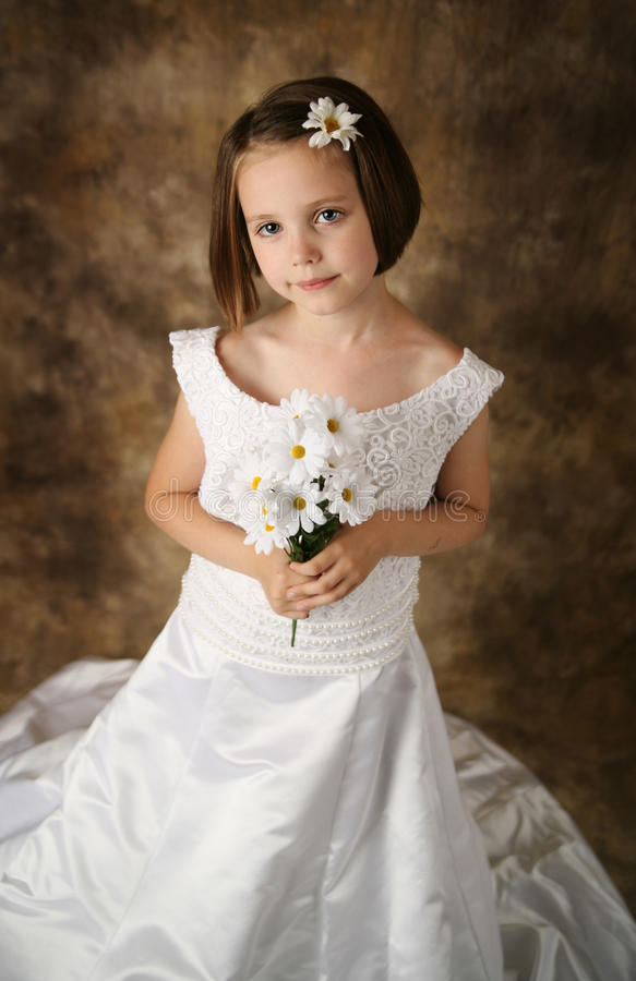 Little girl trying on mommy's wedding dress. Beautiful young female child wearing her mother's wedding dress which is too big for her stock photo