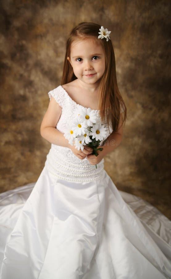 little girl trying on mommys wedding dress stock