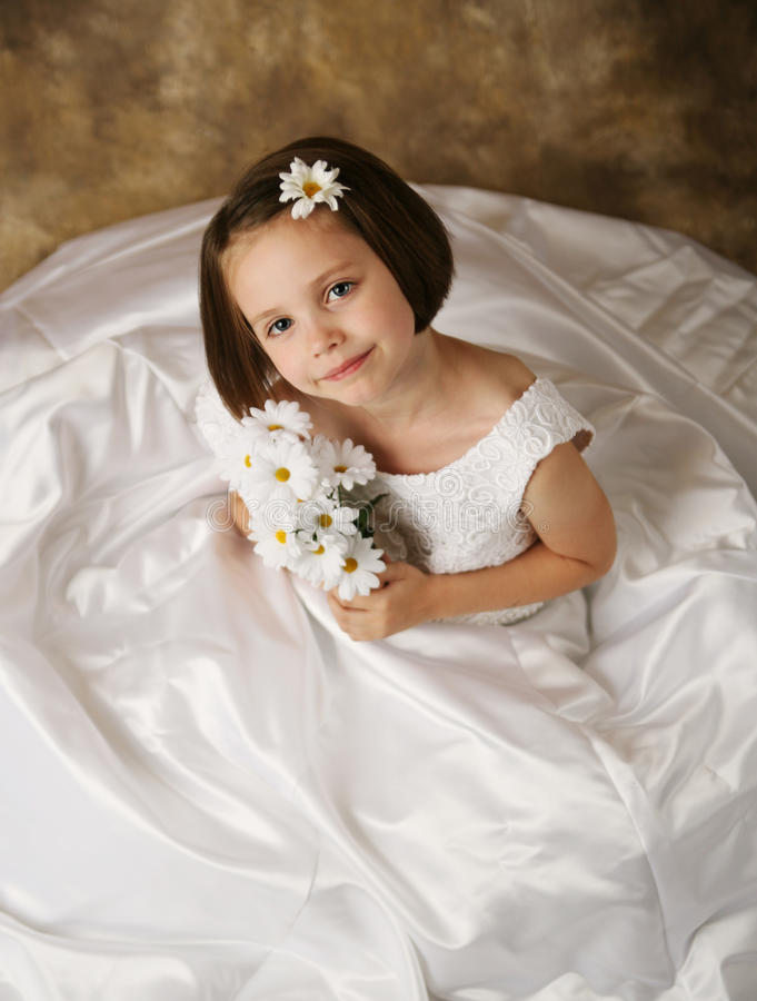 Little girl trying on mommy's wedding dress. Beautiful young female child wearing her mother's wedding dress which is too big for her royalty free stock photography