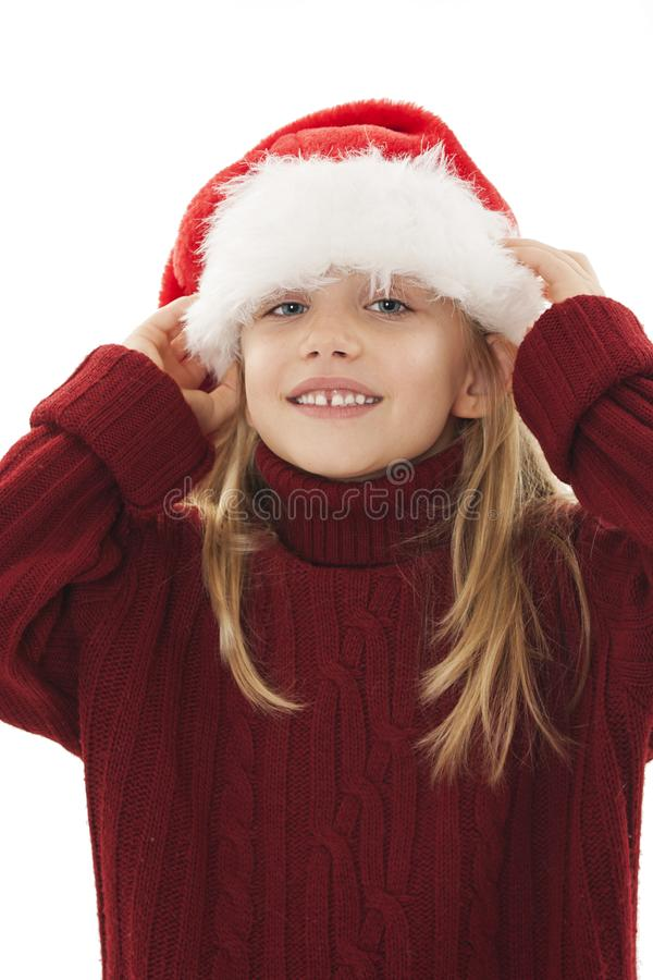 Little girl trying to put Santa Claus hat to head. Joyful Christmas little girl. royalty free stock images