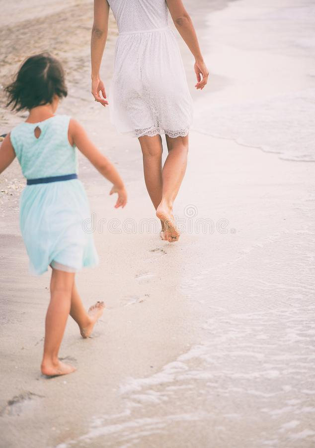 The little girl is trying to walk in the footsteps of her mother. stock photos