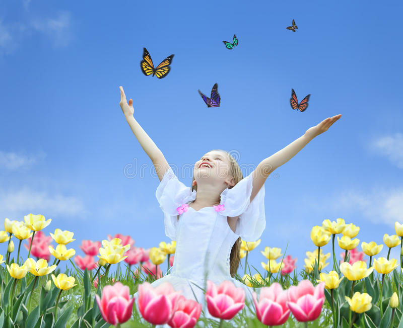Download Little Girl In Tulips With Hands Up And Butterfly Royalty Free Stock Photo - Image: 12540135