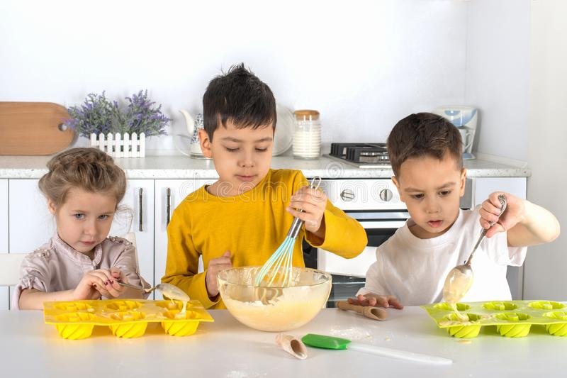 The little girl and two boys cook cake in kitchen of the house. They display dough in silicone molds for baking royalty free stock images