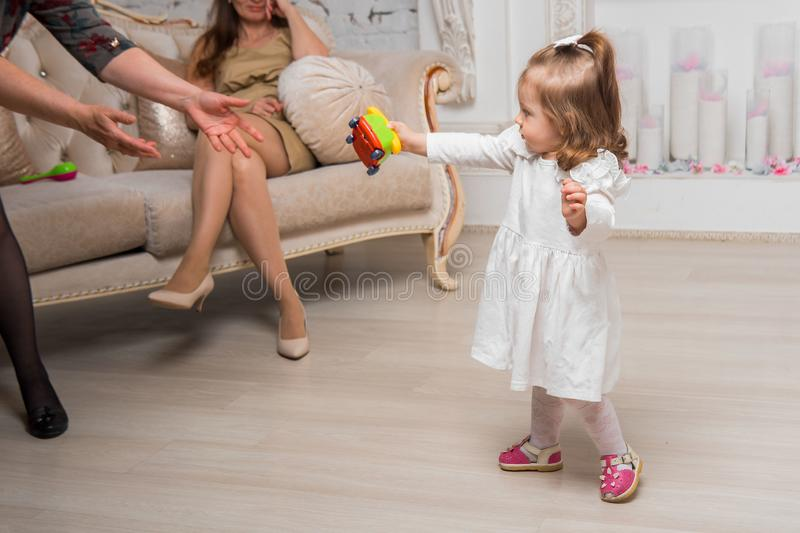 Little girl and two grandmothers. In the guest room they play royalty free stock image