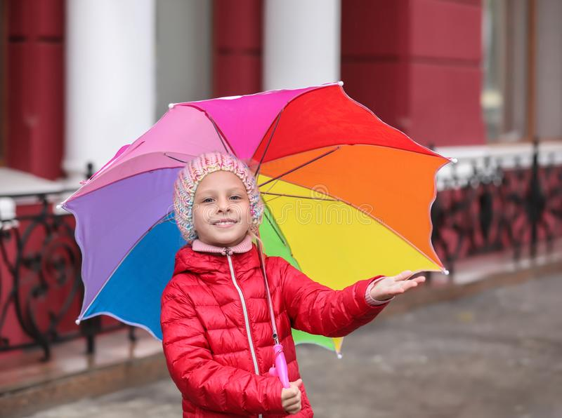 Little girl with umbrella in city on autumn day stock photography