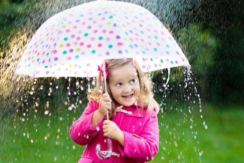 Little girl with umbrella in the rain. Little girl playing in rainy summer park. Child with colorful rainbow umbrella, pink coat walking in the rain. Kid having royalty free stock image