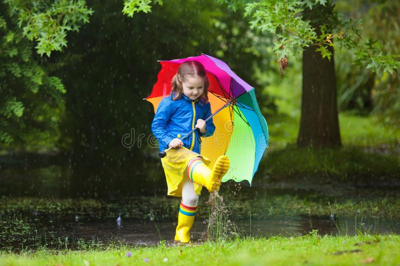Little girl with umbrella in the rain. Little girl playing in rainy summer park. Child with colorful rainbow umbrella, blue coat jumping in muddy puddle, walking royalty free stock photos