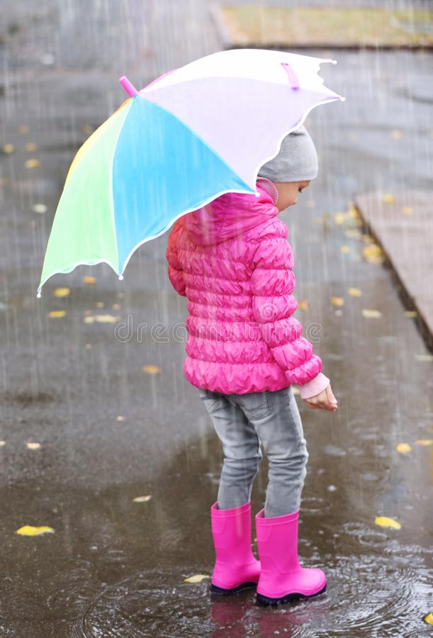 Little girl with umbrella splashing in puddle stock image
