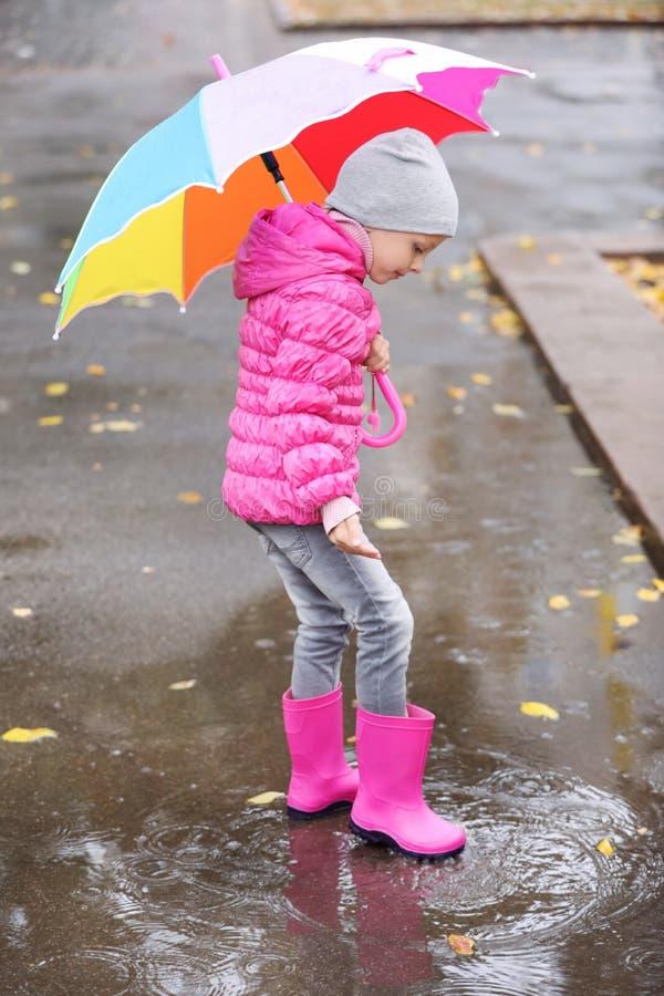Little girl with umbrella splashing in puddle on rainy day. stock images