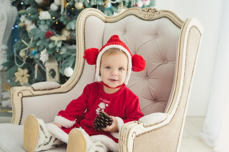 The little girl under the Christmas tree. Baby girl in Santa Claus hat with gifts under Christmas tree at fireplace child decoration kid present xmas beautiful stock photos