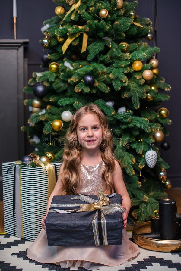 Little girl under the Christmas tree. A girl with gifts under the tree in anticipation of magic. A gift from Santa Claus royalty free stock photography