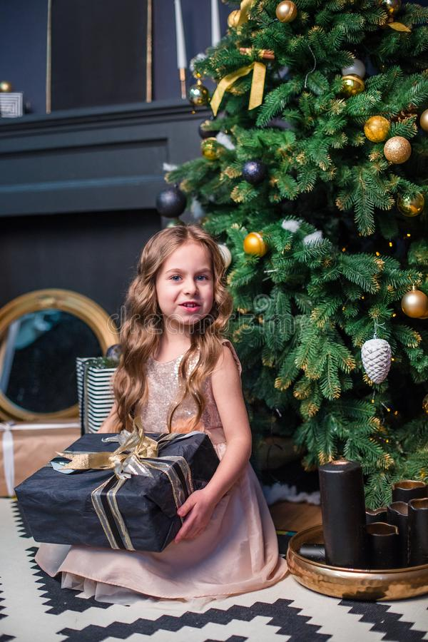 Little girl under the Christmas tree. A girl with gifts under the tree in anticipation of magic. A gift from Santa Claus stock photography