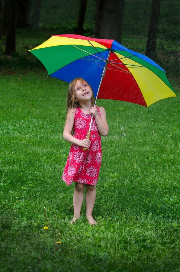 Little girl under colorful umbrella stock image