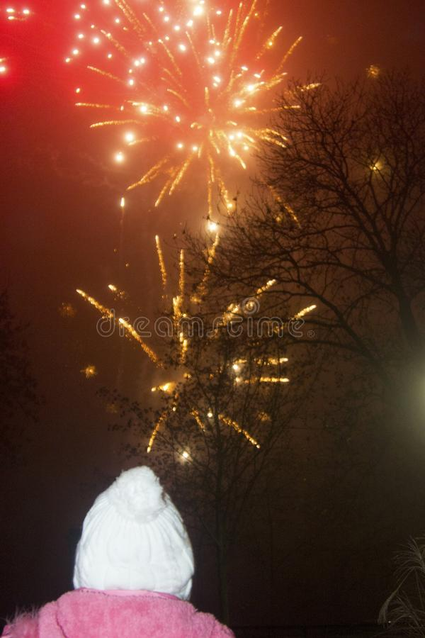 A little girl under fireworks. royalty free stock photography