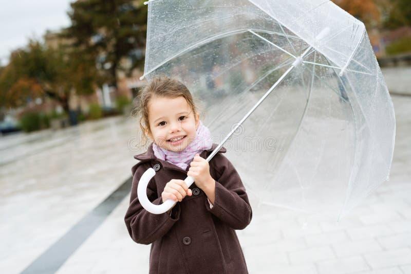 Little girl under the transparent umbrella outside, rainy day. stock photos
