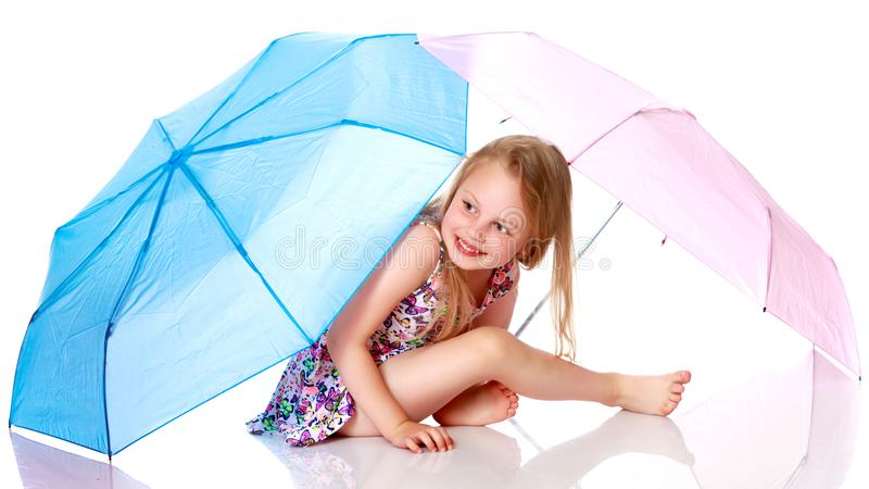 Little girl under an umbrella. royalty free stock photography