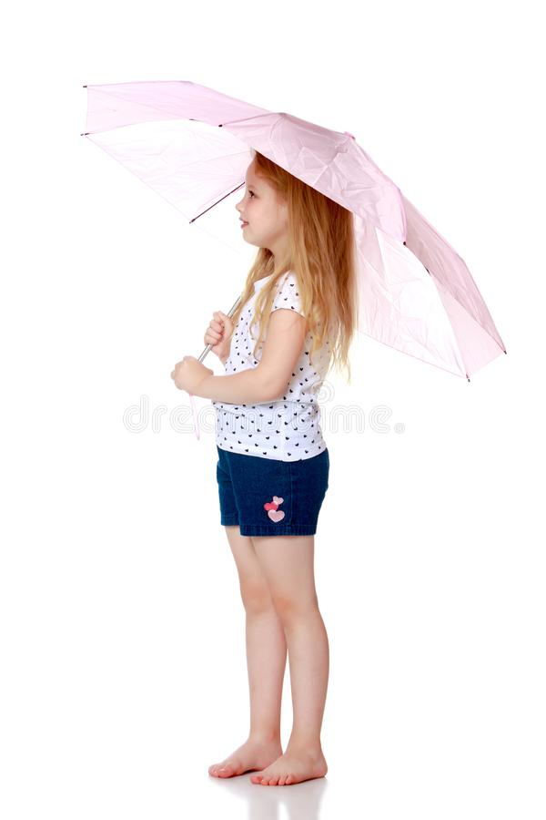 Little girl under an umbrella. stock photo