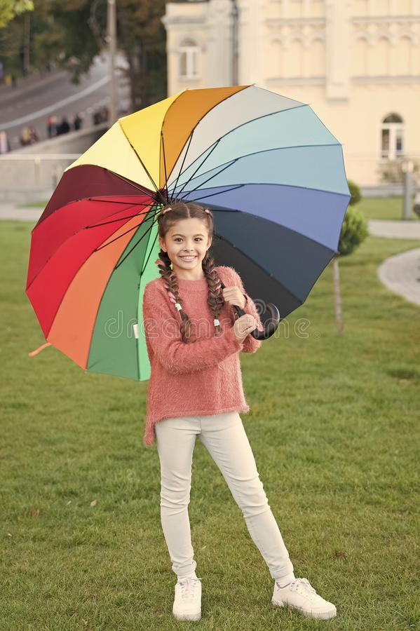 Little girl under umbrella. Rainbow after rain. Optimist and cheerful. Spring style. Positive mood in autumn rainy. Weather. Multicolored umbrella for little royalty free stock image