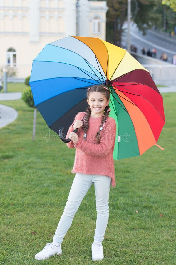 Little girl under umbrella. Rainbow after rain. Optimist and cheerful. Spring style. Positive mood in autumn rainy. Weather. Multicolored umbrella for little royalty free stock images