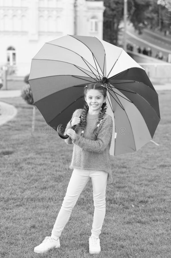 Little girl under umbrella. Rainbow after rain. Optimist and cheerful. Spring style. Positive mood in autumn rainy. Weather. Multicolored umbrella for little stock image
