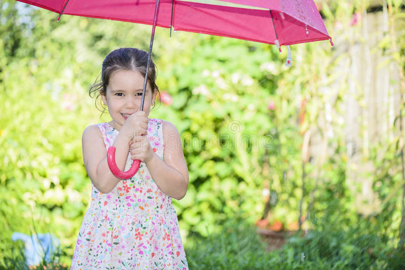 Little girl under umbrella in a rainy summer day stock photo