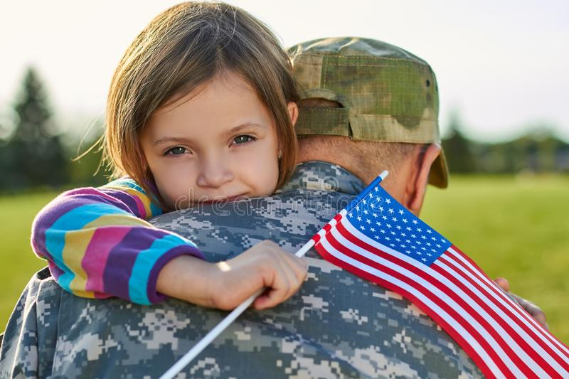 Little girl with US flag is hugging her father. royalty free stock image