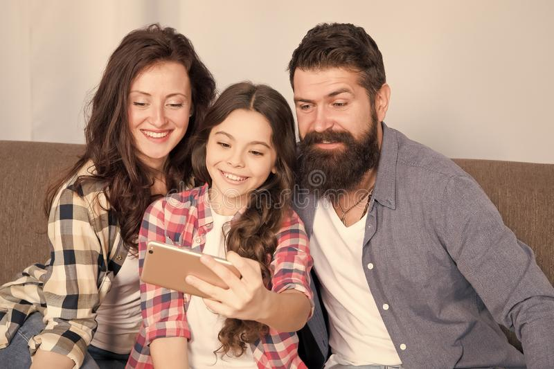 Little girl use smartphone with mother and father. bearded man and woman with little girl. Mother and father make selfie. For little girl. Family with little royalty free stock image
