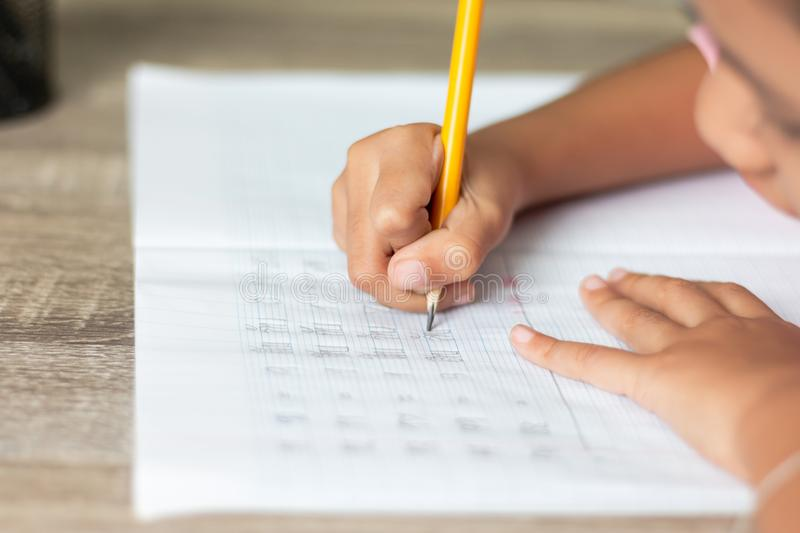 A little girl use a yellow pencil writing in a notebook stock photography