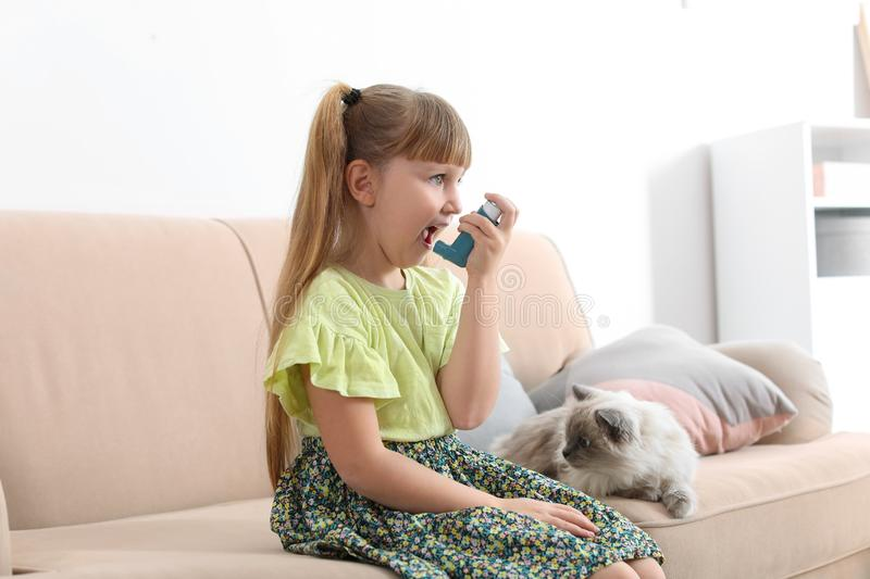 Little girl using asthma inhaler near cat at home royalty free stock photography