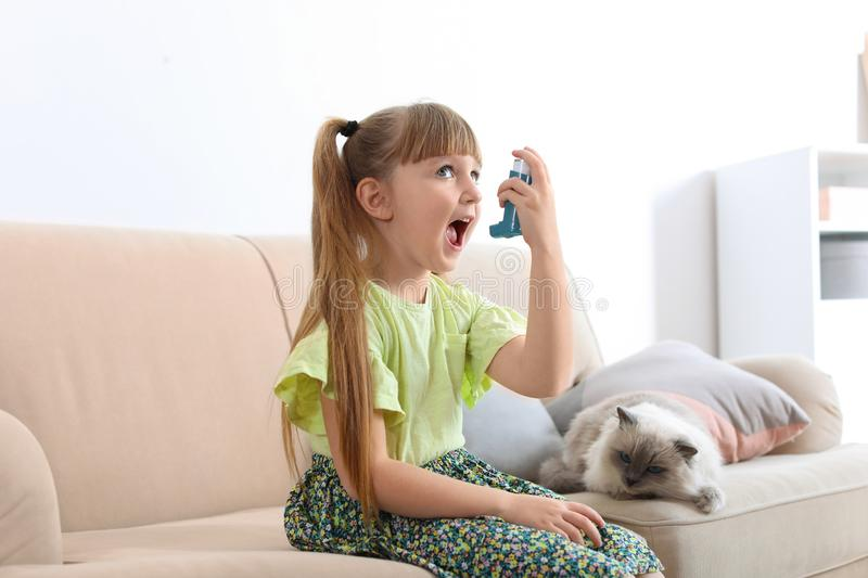 Little girl using asthma inhaler near cat at home stock images