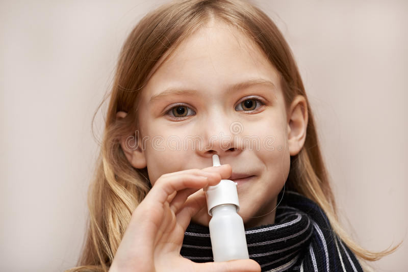 Little girl using nasal drops. Indoors stock images