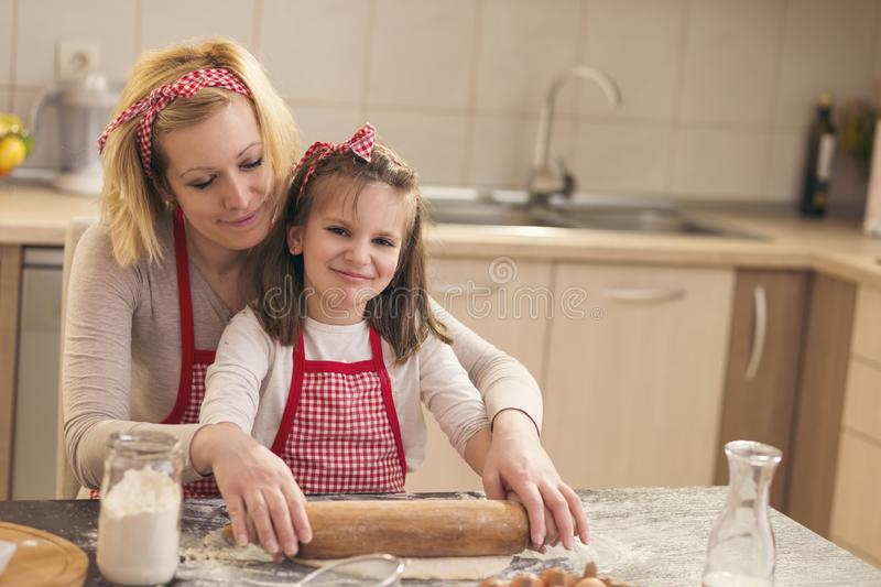 Little girl using rolling pin in the kitchen royalty free stock images