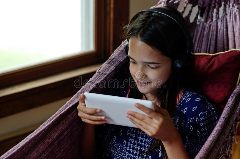 Little girl using a tablet in a hammock stock photography