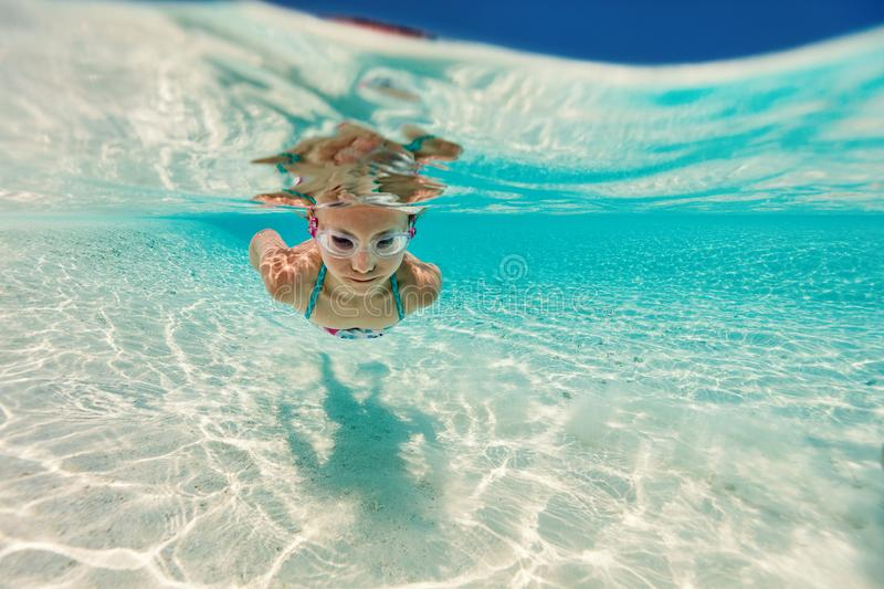 Little girl on vacation. Underwater photo of a little girl swimming in tropical ocean royalty free stock photos