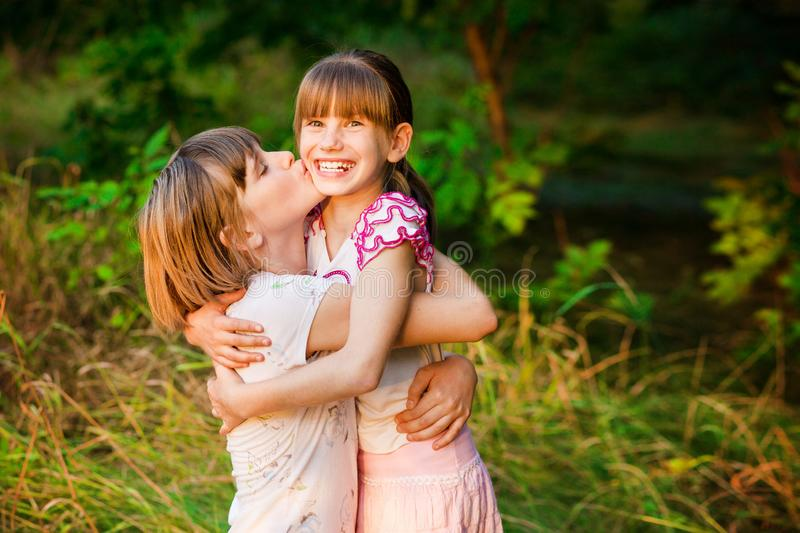 Little girl is very happy that she has sister. Loving sister hugging cute little girl showing love care support. stock image