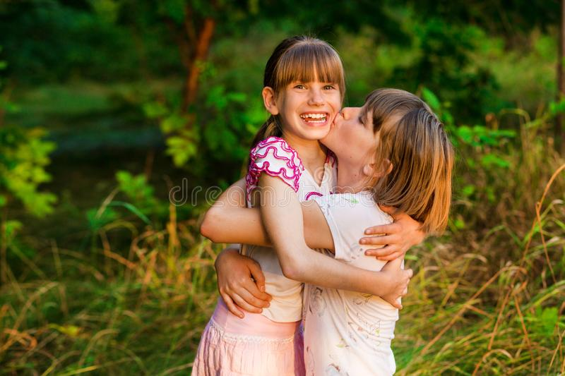 Little girl is very happy that she has sister. Loving sister hugging cute little girl showing love care support. royalty free stock photography