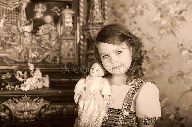 Little girl with a vintage doll in her hands royalty free stock photos