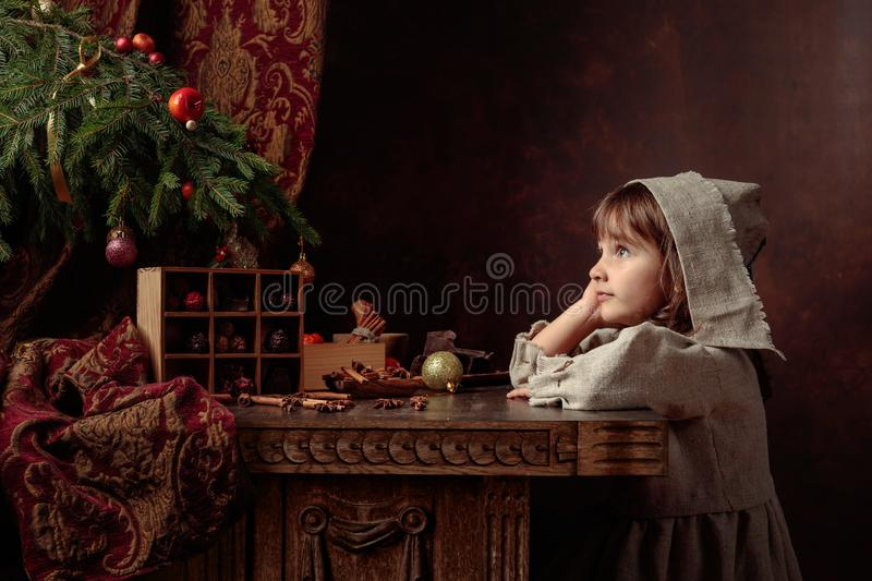 Little girl in an vintage linen dress dreaming near the table with sweets. Genre portrait in retro style royalty free stock photos