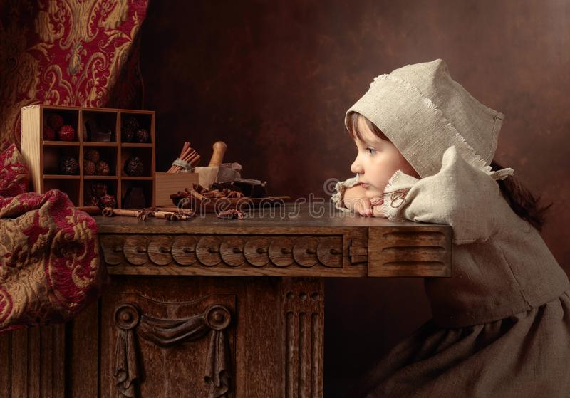 Little girl in an vintage linen dress dreaming near the table with sweets. Genre portrait in retro style stock photo