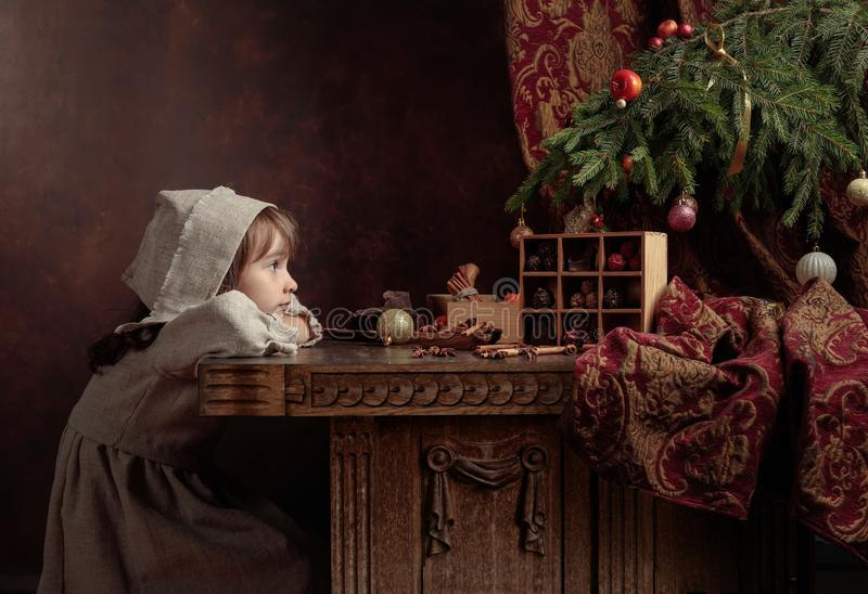 Little girl in an vintage linen dress dreaming near the table with sweets. Genre portrait in retro style royalty free stock photo