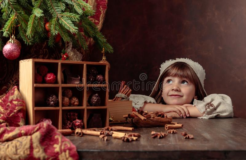 Little girl in an vintage linen dress dreaming near the table with sweets. Genre portrait in retro style royalty free stock photography