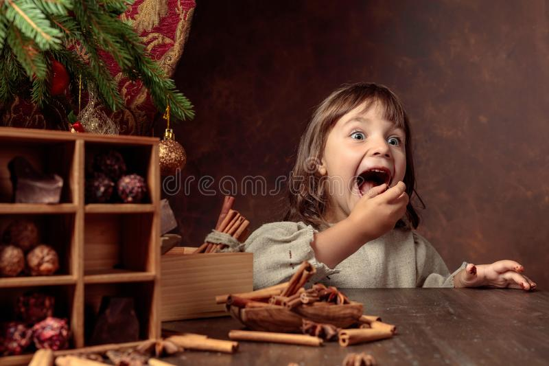 Little girl in an vintage linen dress near the table with sweets. Genre portrait in retro style royalty free stock images