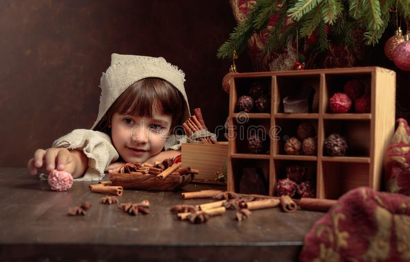 Little girl in an vintage linen dress near the table with sweets. Genre portrait in retro style stock photos