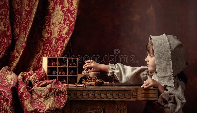Little girl in an vintage linen dress near the table with sweets.  Genre portrait in retro style stock photography
