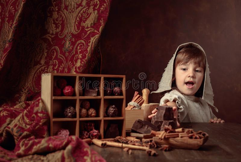 Little girl in an vintage linen dress near the table with sweets.  Genre portrait in retro style stock image