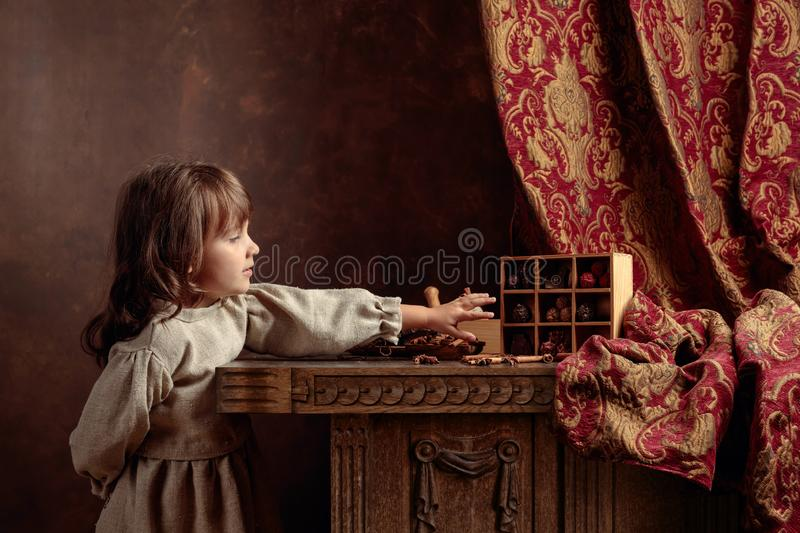 Little girl in an vintage linen dress near the table with sweets.  Genre portrait in retro style royalty free stock photography