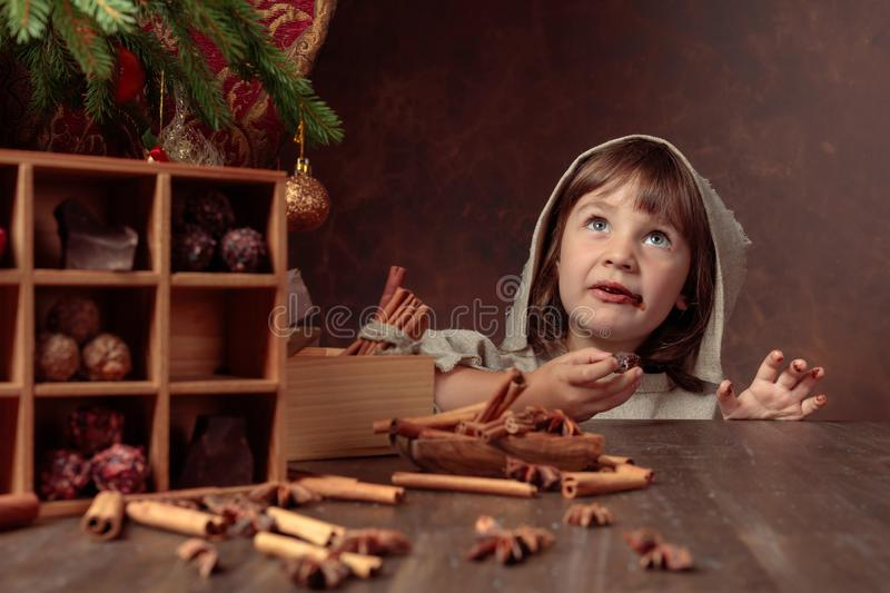 Little girl in an vintage linen dress near the table with sweets. Genre portrait in retro style royalty free stock image